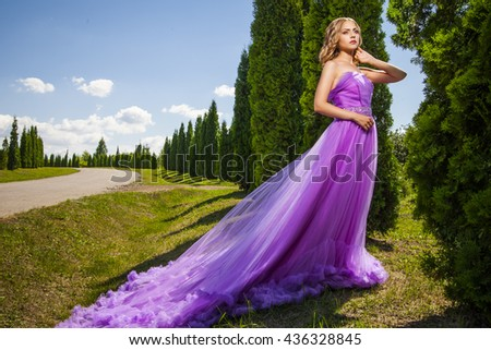 Elegant woman in violet long dress against of green alley