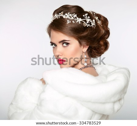 Elegant woman in white fur coat. Wedding Hairstyle. Beautiful fashion bride girl model portrait. Luxury jewelry. Attractive young woman with red hair.