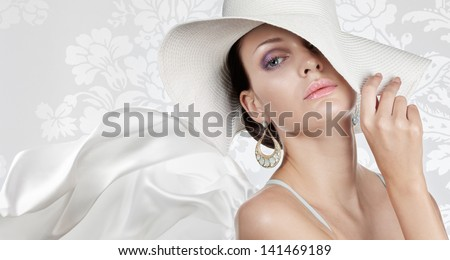 Elegant woman in white hat on white fancy background - stock photo
