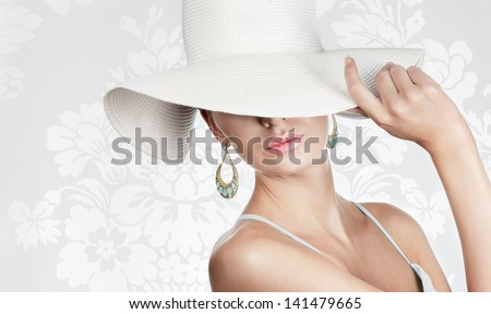 Elegant woman in white hat on white fancy background. Space for text. - stock photo