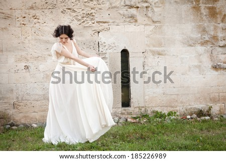 Elegant woman in white long dress looking down while holding the sides of her dress. - stock photo