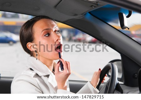 elegant woman is doing makeup on the run in her car - stock photo