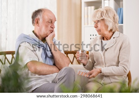 Elegant woman is reminding her husband about taking medicine