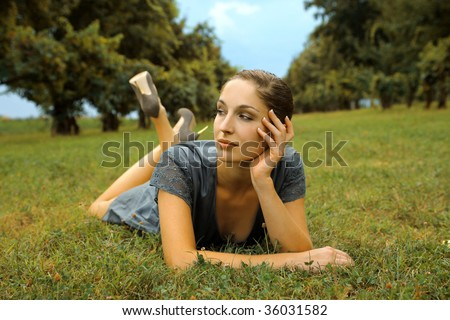 elegant woman laying on lawn - stock photo