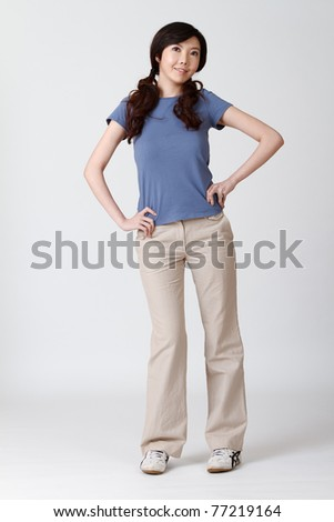Elegant woman of Asian, full length portrait isolated on gray studio background.