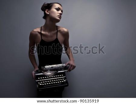 Elegant woman pose with ancient typewriter. Conceptual fashion photo. - stock photo