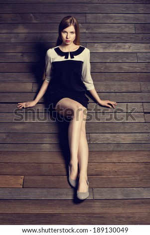 elegant woman posing in a black and white dress on wood. Outdoor - stock photo