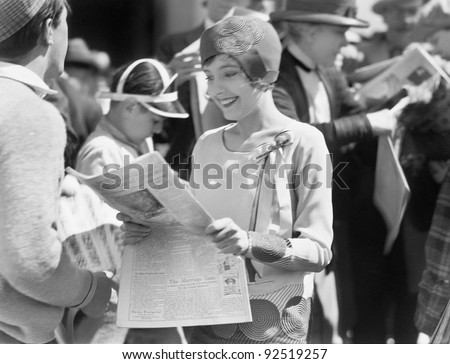 Elegant woman reading a newspaper - stock photo