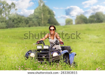 Elegant woman riding quatrocycle quadrocycle  - stock photo