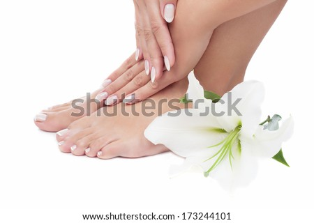 Elegant woman's manicured hand and pedicured feet with madonna lily on bamboo mat