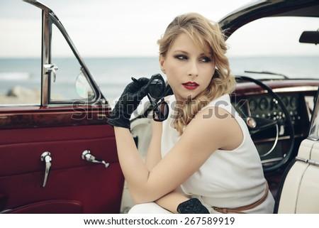 Elegant woman sitting in vintage car - stock photo
