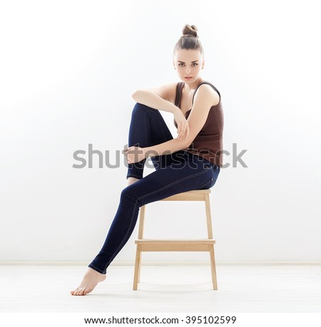 Elegant woman sitting on a chair in blue jeans in the studio