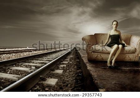 elegant woman sitting on a sofa near to train tracks - stock photo