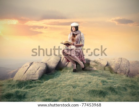 Elegant woman sitting on a stone and reading a book - stock photo