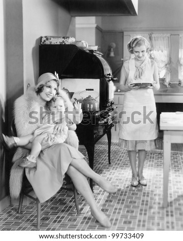 Elegant woman sitting with her baby in a kitchen while a friend is bringing a pie