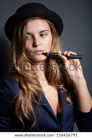 Elegant woman smoking e-cigarette, wearing suit and hat