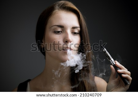 Elegant woman smoking e-cigarette with smoke portrait - stock photo