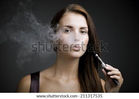 Elegant woman smoking e-cigarette with smoke portrait - stock photo
