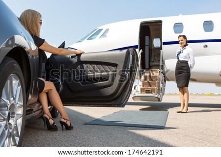Elegant woman stepping out of car parked in front of private plane and airhostess - stock photo
