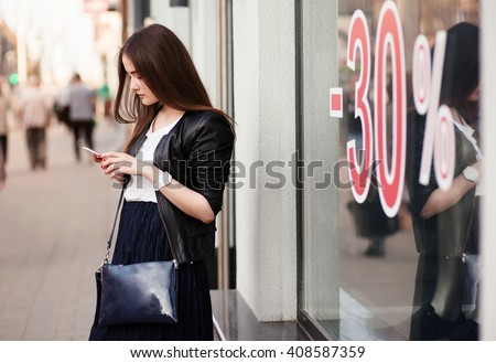 Elegant woman using a mobile phone in front of showcase boutiques. Discount from 30 percent. - stock photo