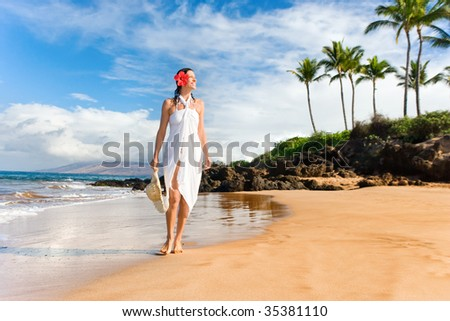 elegant woman walking along tropical beach with palm trees - stock photo