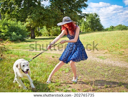 Elegant woman walking her big dog in the park,  Serbia.