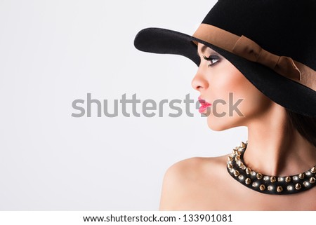 Elegant woman wearing black hat and necklace - stock photo