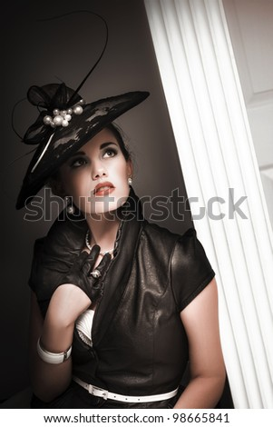 elegant woman wearing black hat with pearls, black leather blouse and black half gloves leaning on a door post - stock photo