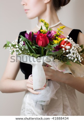 Elegant woman with a bouquet of flowers - stock photo