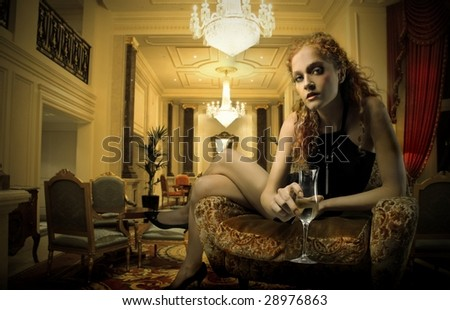elegant woman with a glass of wine in a luxury interior - stock photo