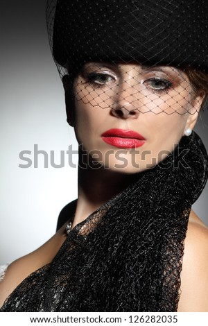 elegant woman with a hat on gray background