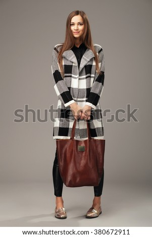Elegant woman with a leather brown fashion bag