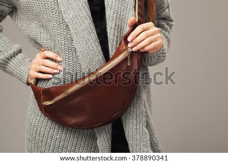 Elegant woman with a leather fanny pack. Closeup picture