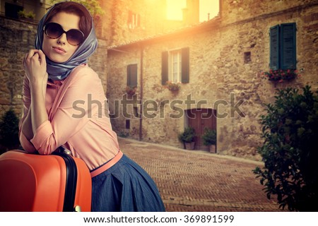 Elegant woman with a orange suitcase travel on street of italian city
