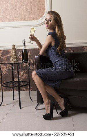 elegant woman with blue dress and heels is sitting on sofa in chic ambient and taking a flute of champagne in the hand