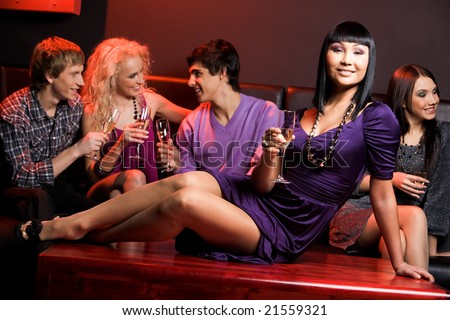 Elegant woman with champagne sitting on table on background of chatting people