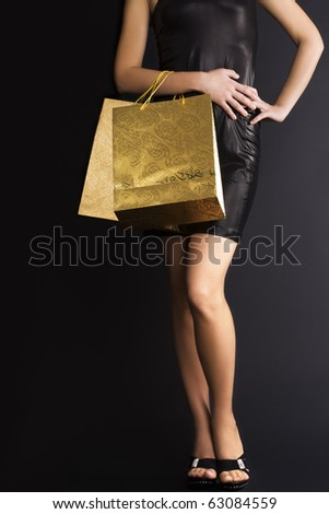 Elegant woman with golden holiday shopping bags. Space for text. - stock photo