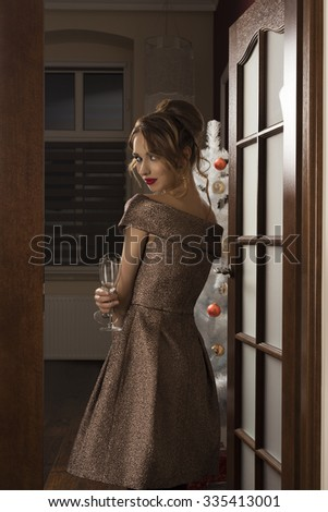 elegant woman with golden shiny dress and hair-style posing turned on her back in indoor portrait in christmas night with glasses in the hand for toast. Christmas tree and gift boxes on background - stock photo