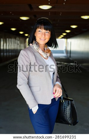 Elegant woman with handbag. Young woman of thirty years with hairstyle, on backlight bulbs background, Positive human emotion, facial expression - stock photo