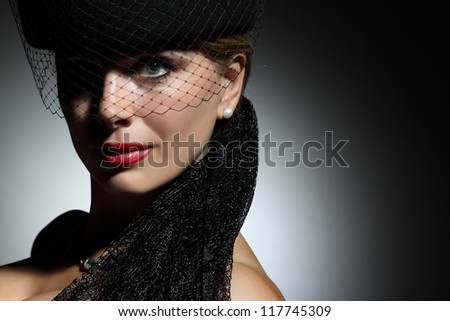elegant woman with hat on a gray background