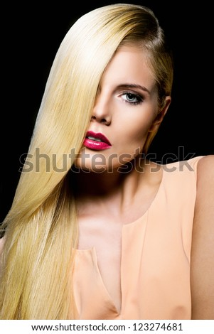elegant woman with healthy hair against black background