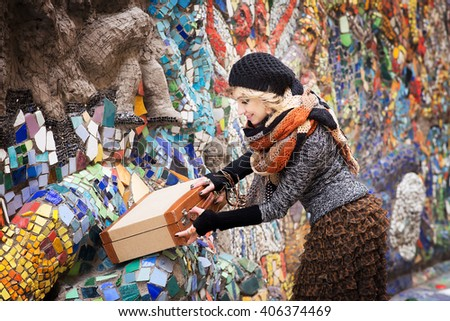 Elegant woman with scarf and beret open suitcase
