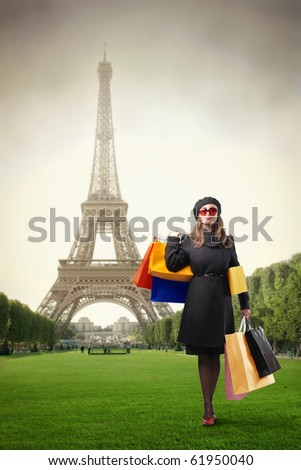 Elegant woman with shopping bags standing in a park with Eiffel Tower on the background - stock photo