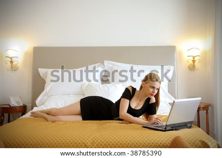 elegant woman working with laptop on a luxury bed - stock photo