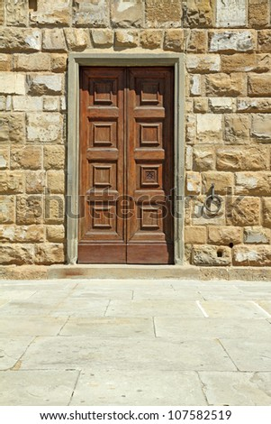 elegant wooden door and stone wall, detail of facade of  town hall of Florence, Piazza Signoria, Italy, Europe - stock photo