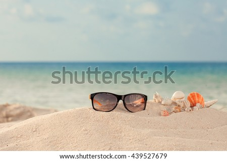 Elegant yellow and black women's sunglasses with shell at the beach and blue ocean - stock photo
