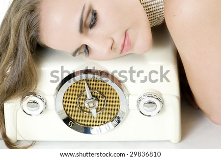 Elegant Young Beauty Listening to Love Songs on a Vintage Radio. - stock photo