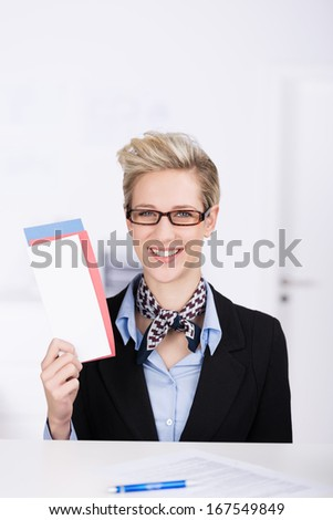 Elegant young blond travel hostess or receptionist with a ticket in her hand smiling as she tries to attract the attention of a client - stock photo