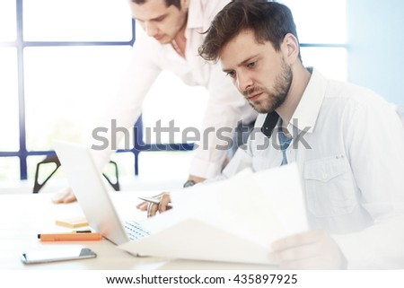 Elegant young businessman analyzing data in office - stock photo