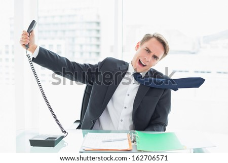 Elegant young businessman shouting as he holds out phone at a bright office